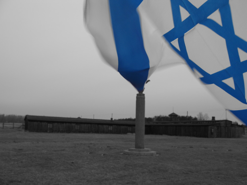 Rising from the ashes. An Israeli Flag billows into the frame and kisses the a peak of amonumental pillar atMadajnek Concentration Camp,Poland.