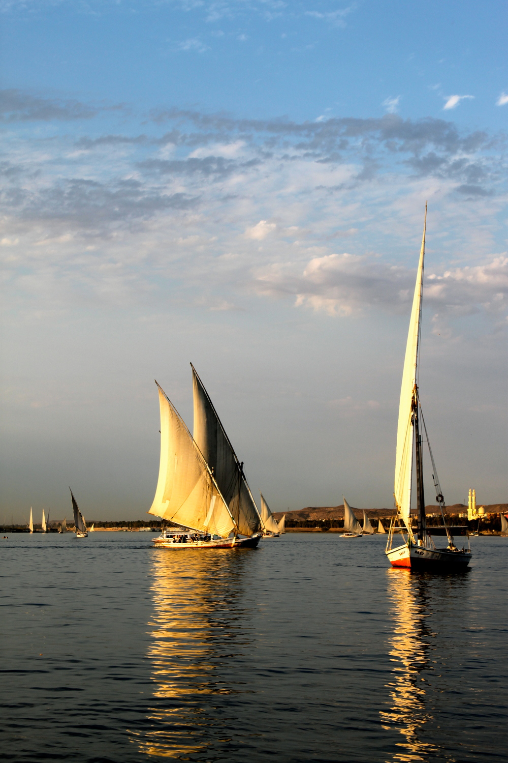 Feluccas floating down the nile at sunset in Aswan, Egypt.
