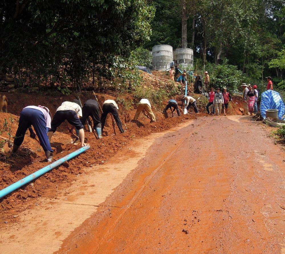 Villagers laying the pipeline from the storage tanks to the village