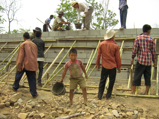 Pouring the concrete into the block formwork ( The little boy in the photo was the baby in the story in the introduction section. He was the catalyst for the project and ended up helping out)
