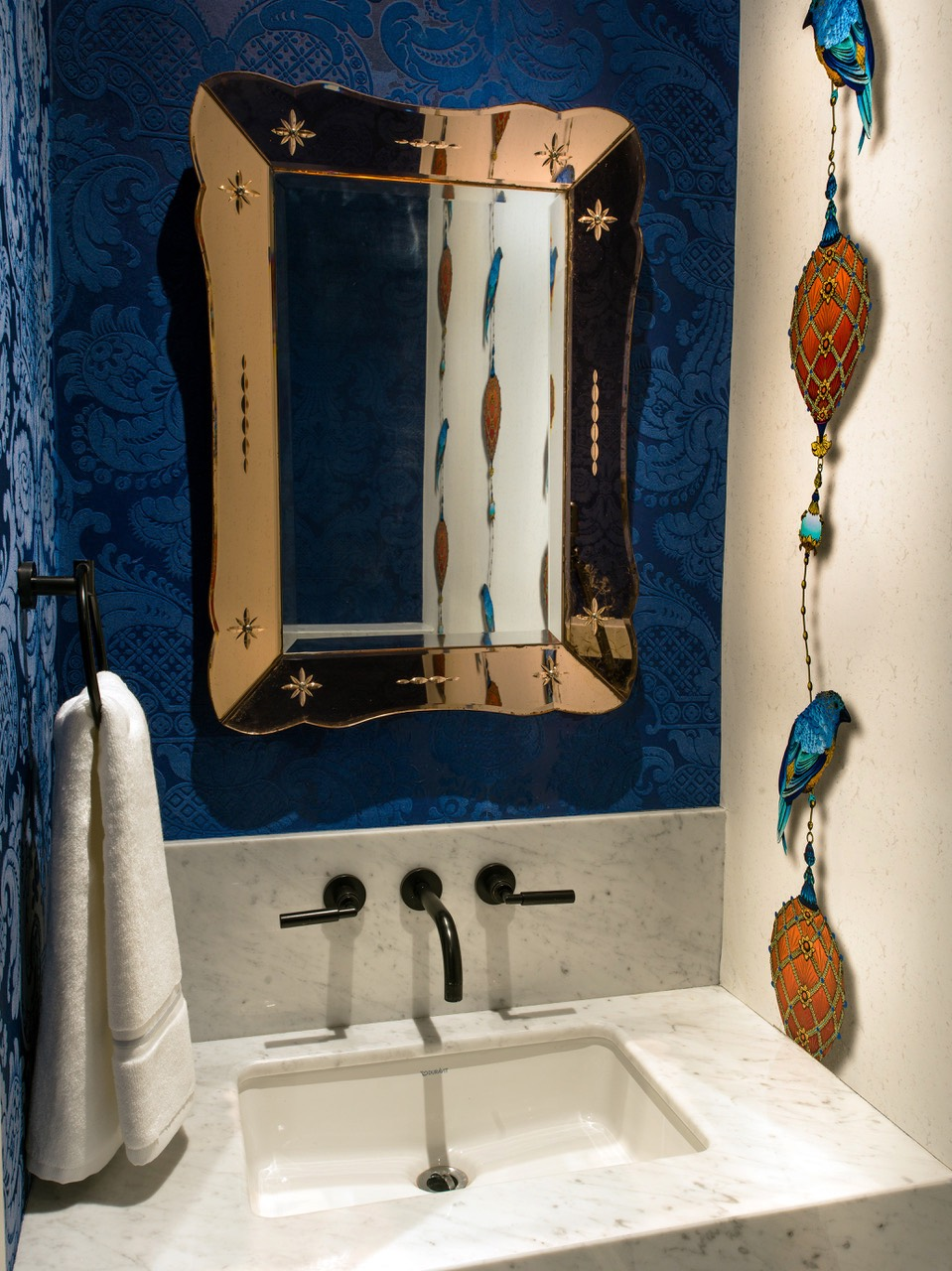 Powder room with Vintage mirror and not one but two fabulous wall papers. (Kit Miles & Cole & Son)