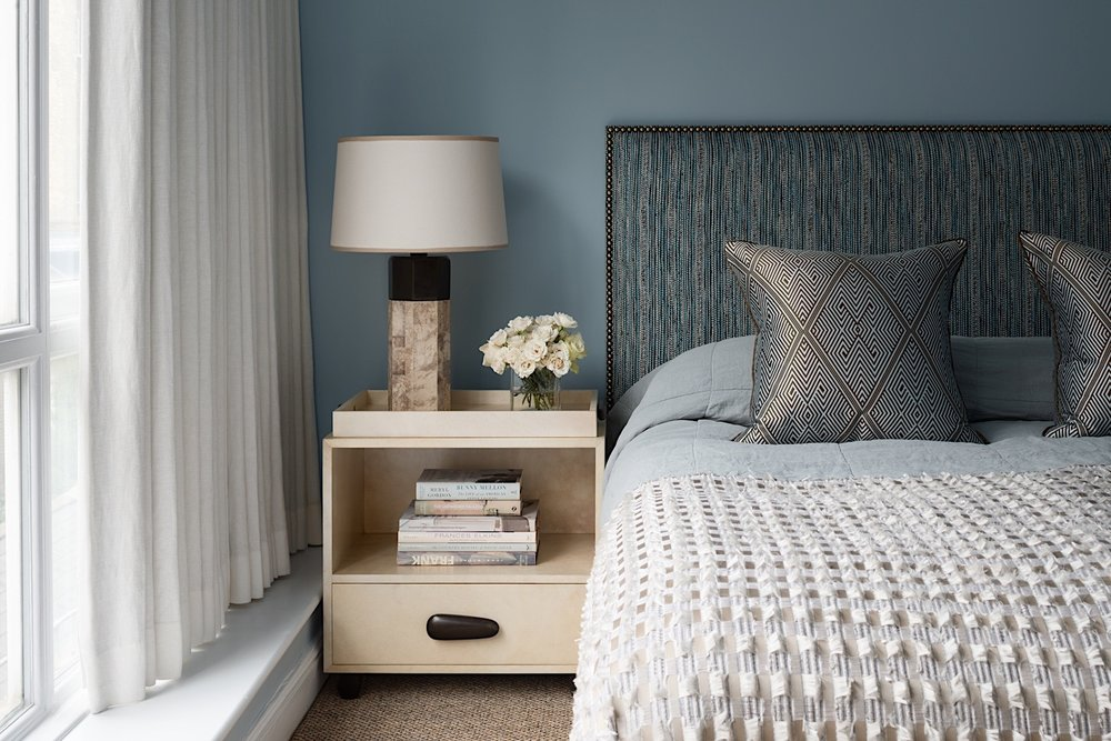 Bespoke headboard in a Toyine Sellers material, bronze & shagreen table lamp and parchment & bronze bedside table by Alexander Lamont. Hand woven silk cushions by Oro.