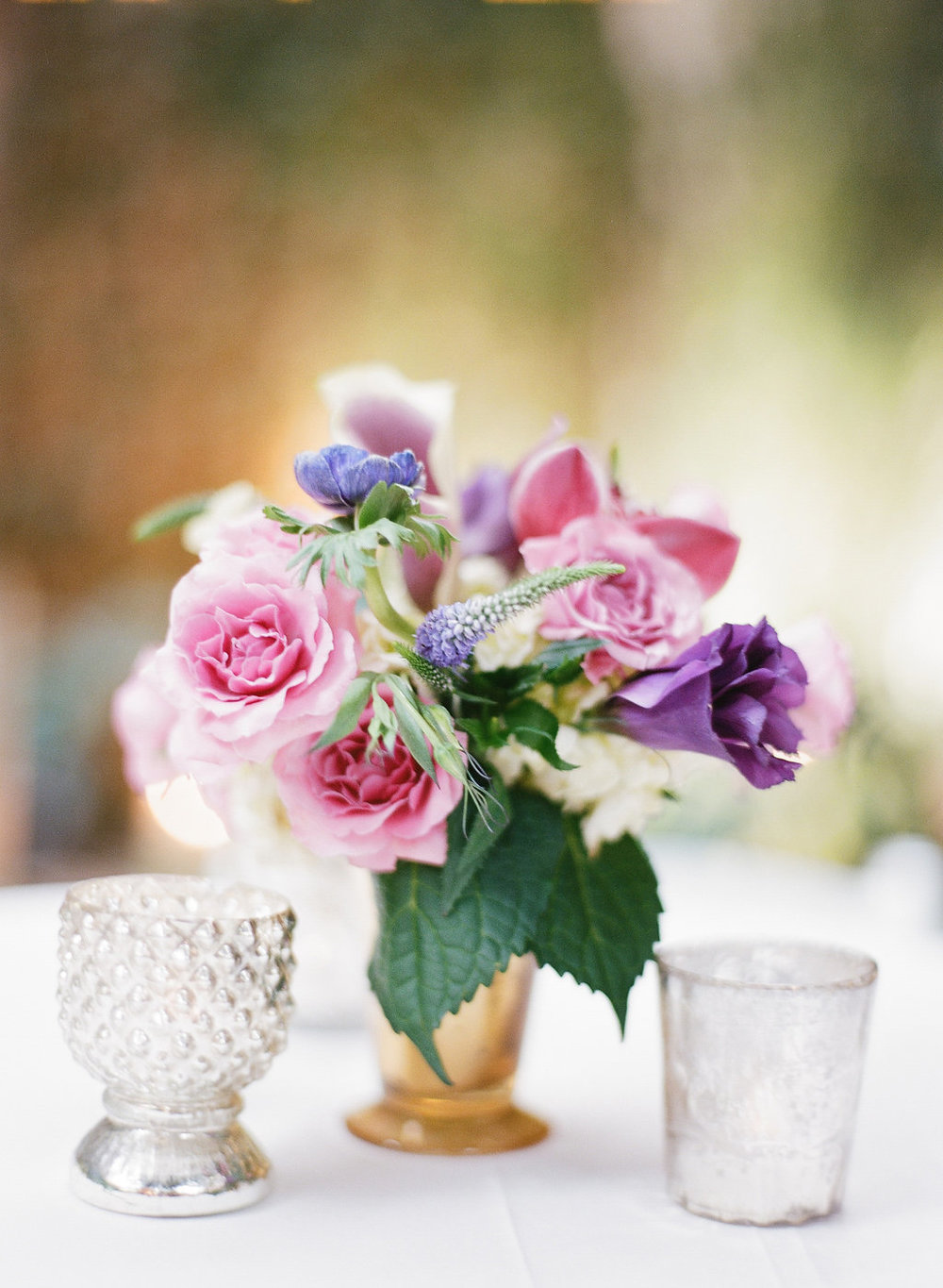 Purple and Violet cocktail table arrangements | This is what happens when a bride asks her guests to wear all white | Wedding En Blanc | Sapphire Events | Erika Parker Photography Montegut House | Luxury Wedding | Courtyard wedding | French Quarter Wedding | Luxe Wedding Details | Kim Starr Wise Florals