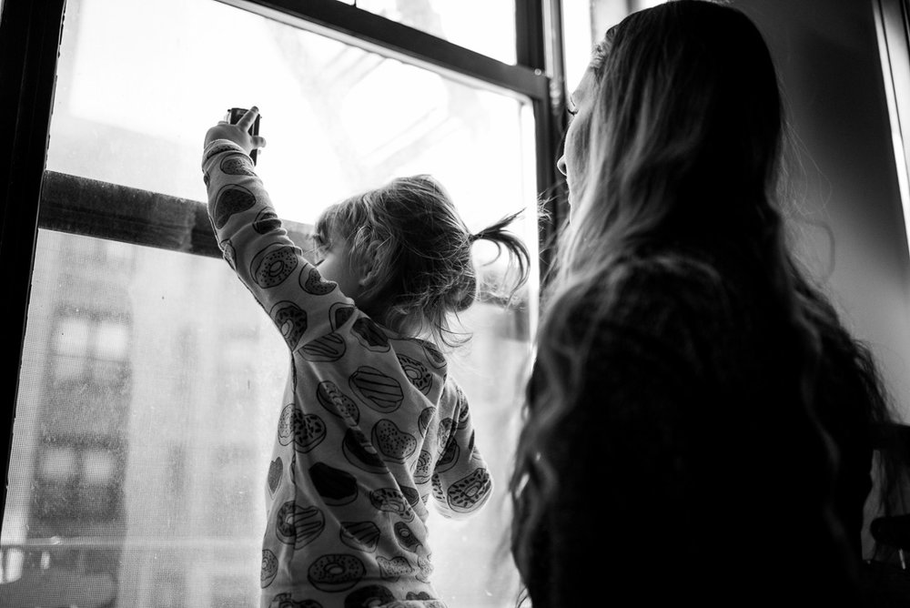 Toddler girl plays at window while mom watches
