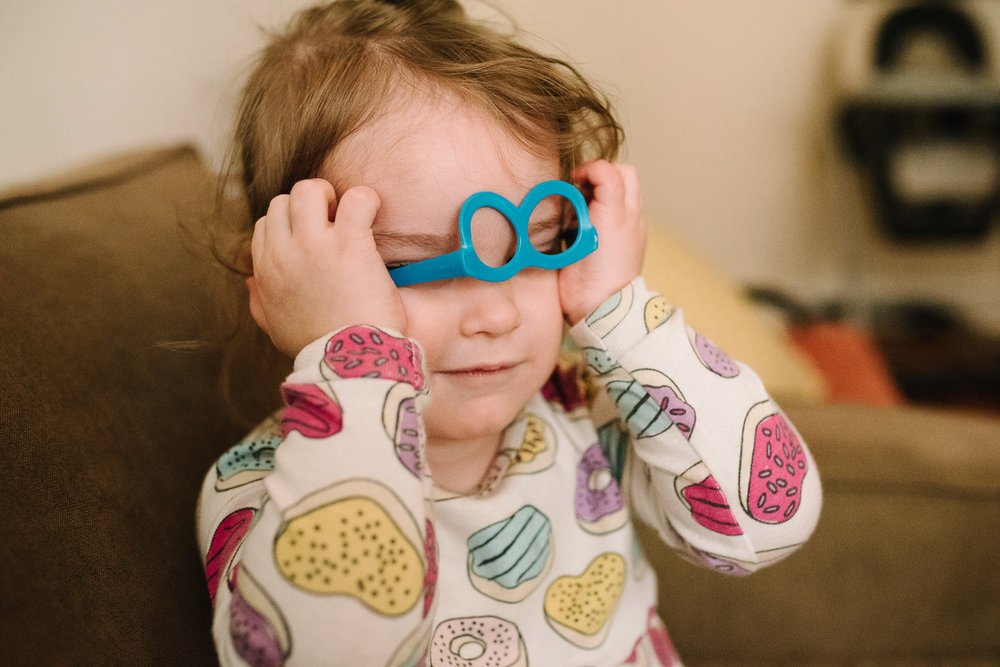 Little girl in donut pajamas puts on a blue pair of plastic glasses upsidedown