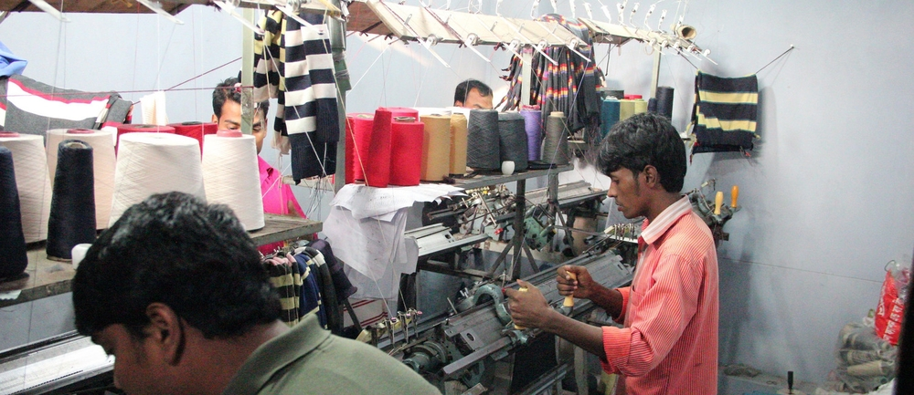 Workers knit cloth to be used in garment production in a rented room of an unregistered manufacturing facility. Photo credit Nayantara Banerjee, December 2014