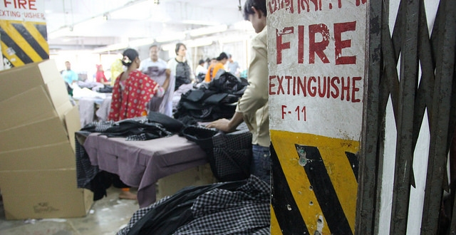 A fire extinguisher is conspicuously absent inside a factory where clothing and boxes, potential fuel sources, are stacked on the floor. Photo Credit Bishawjit Das.
