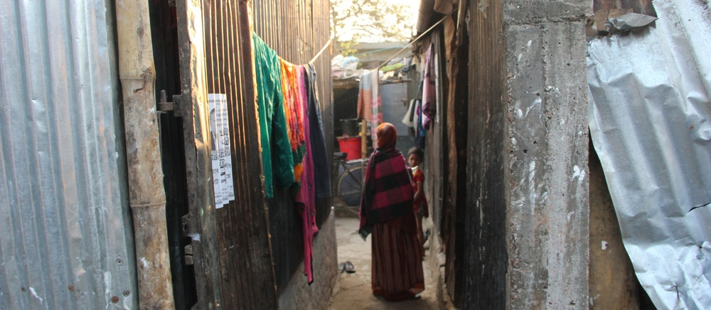 A woman walks through a neighborhood where many garment workers live in Dhaka. Photo credit Bishawjit Das