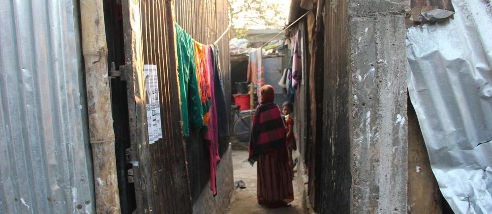 A woman walks through a neighborhood where many garment workers live in Dhaka. Photo creditBishawjit Das