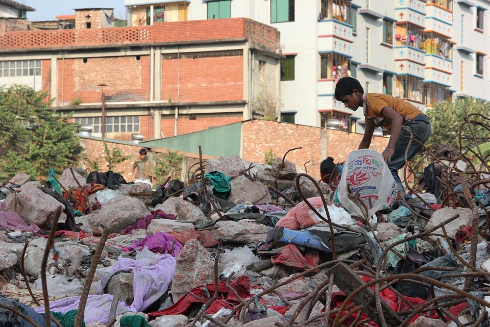A boy picks over the rubble of Rana Plaza, February 2014. Photo credit: Bishawjit Das.
