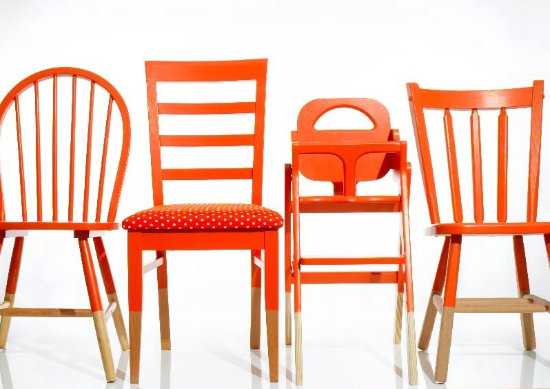 Mismatched chairs painted the same color unite around a table.