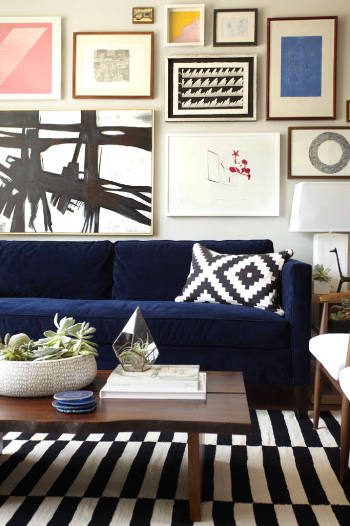 This graphic art collection has a distinct feel of being thoughtfully collected over time. The bold black-and-white pieces match the pillow and rug, and pops of color add life to the room.