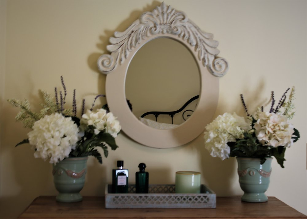 You can easily artfully layer a small space such as a dresser top.  Here we flanked the antique mirror with matching vases of silk flowers.  Then added a small tray for trinkets.  Using different shades of neutral colors adds to the continuity.  The small sprigs of lavender in the flowers adds a pop of color.