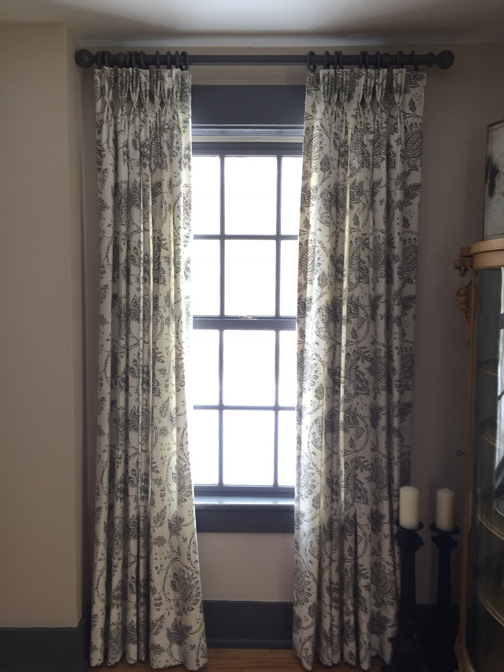 These cotton linen panels are made from a  Kravet  fabric with pinch pleats.  They are in a dining room and help to muffle sound.  The drapery rod and rings were painted the color of the trim ( Benjamin Moore  Kendall Charcoal) which is a close match to the grey in the fabric.