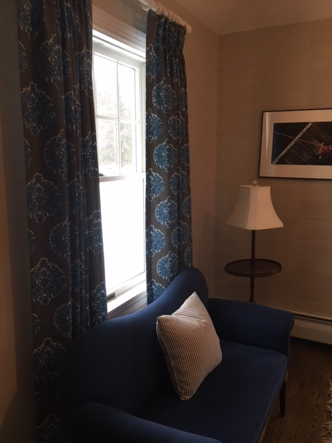The medallion pattern on these drapes plays off the blue in the sette and the dark grain of the floor.