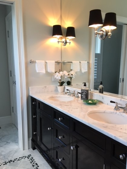 This is one of our favorites...wall to wall mirror glass, double sinks, marble top, lever handle faucets and high gloss vanity!