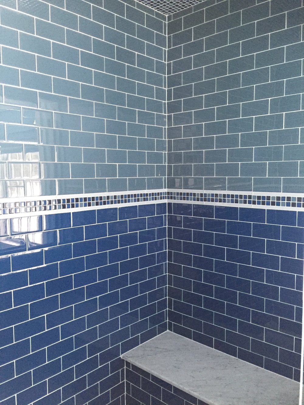 What about a bench in the shower?  We matched the bench top to the vanity tops...local marble!  We also tiled the ceiling of the shower using the small glass tile in the decorative band.  Its a colorful surprise once you're in the shower!