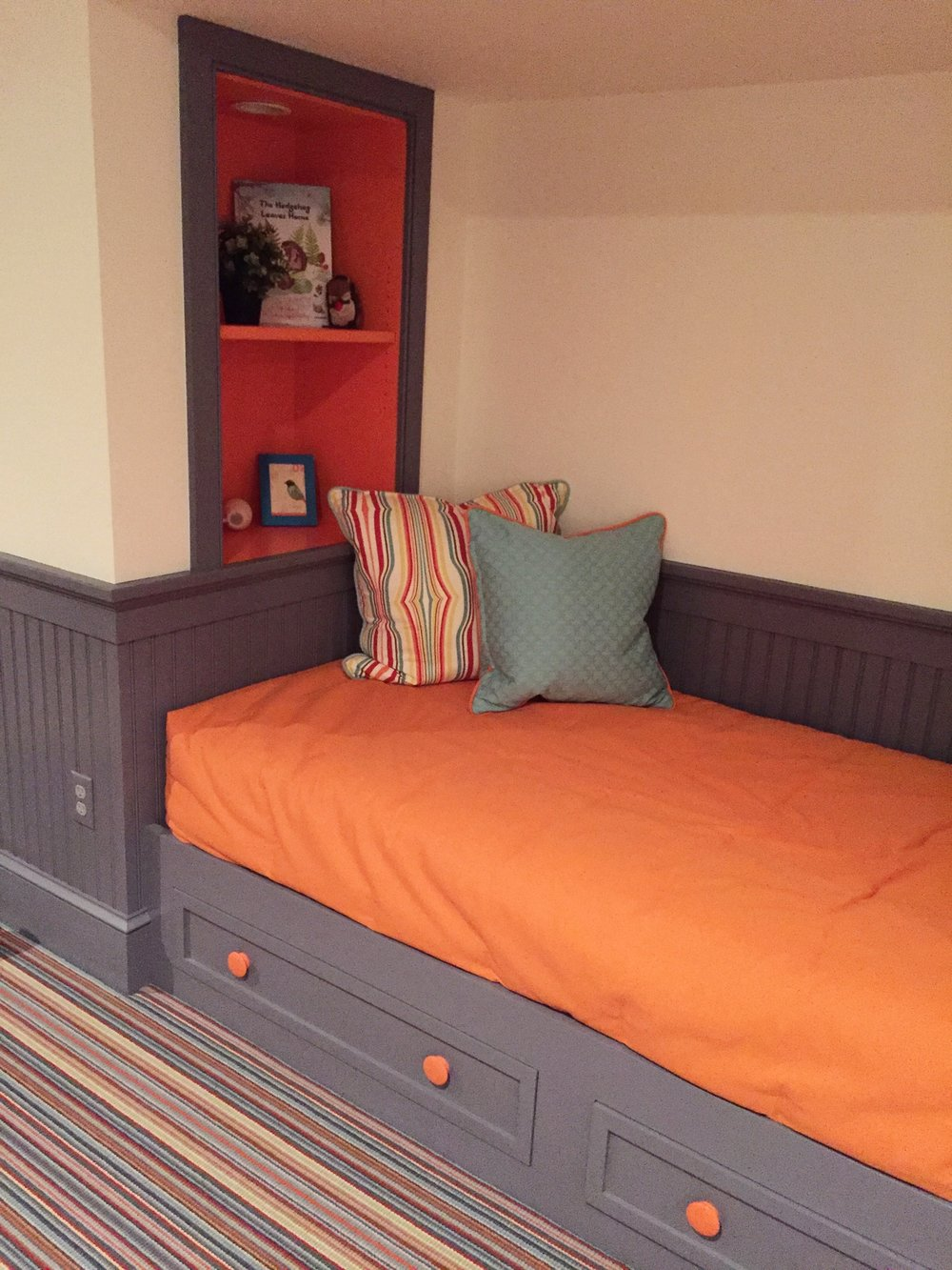 These built in daybeds are ready for any preteen and can take them all the way through high school.  The built in shelves have a charging station (you've got to keep your devices charged!) plus a dimmable night light (for those afraid of the dark...come on, you know who you are!)  The grey and orange paint can be made more masculine or feminine with pillows and bedding.