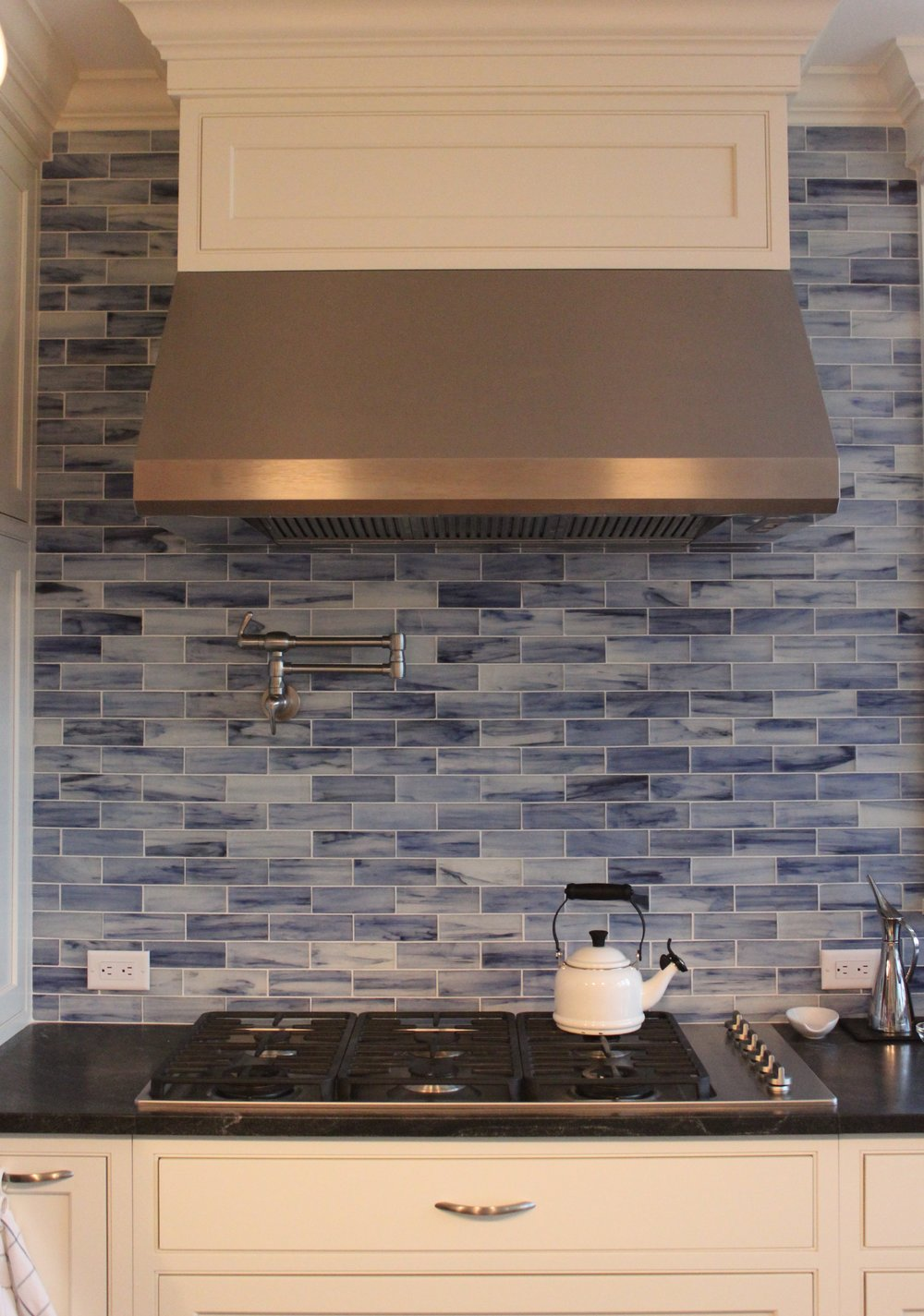 Initially, our client wasn't sure she should take this glass subway tile to the ceiling.  But we're so glad she did.  I love how it highlights the detail in the hood and the crown molding.