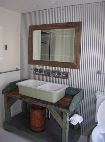 This kids bathroom gets lots of use.  We re-purposed an old work bench with an antique double sink and 2 faucets.  The galvanized, corrugated wall back splash/wall is functional and fun!