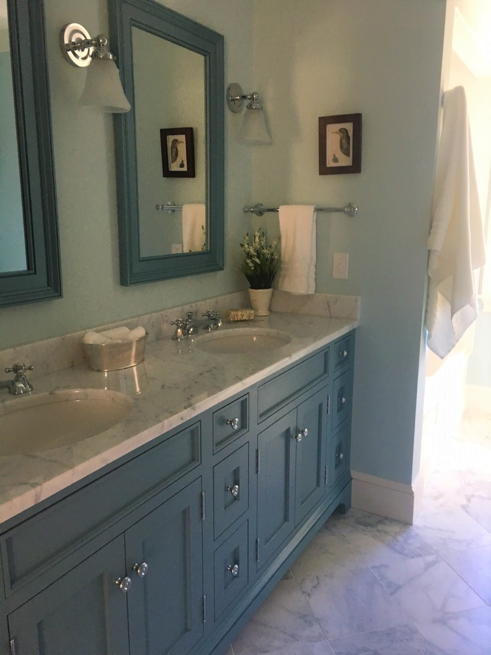 Benjamin Moore's  Province Blue on the vanity is a nice compliment to Ben Moore's Summer Shower on the walls.  These colors, along with the marble floor and vanity top help to create this relaxing bathroom.