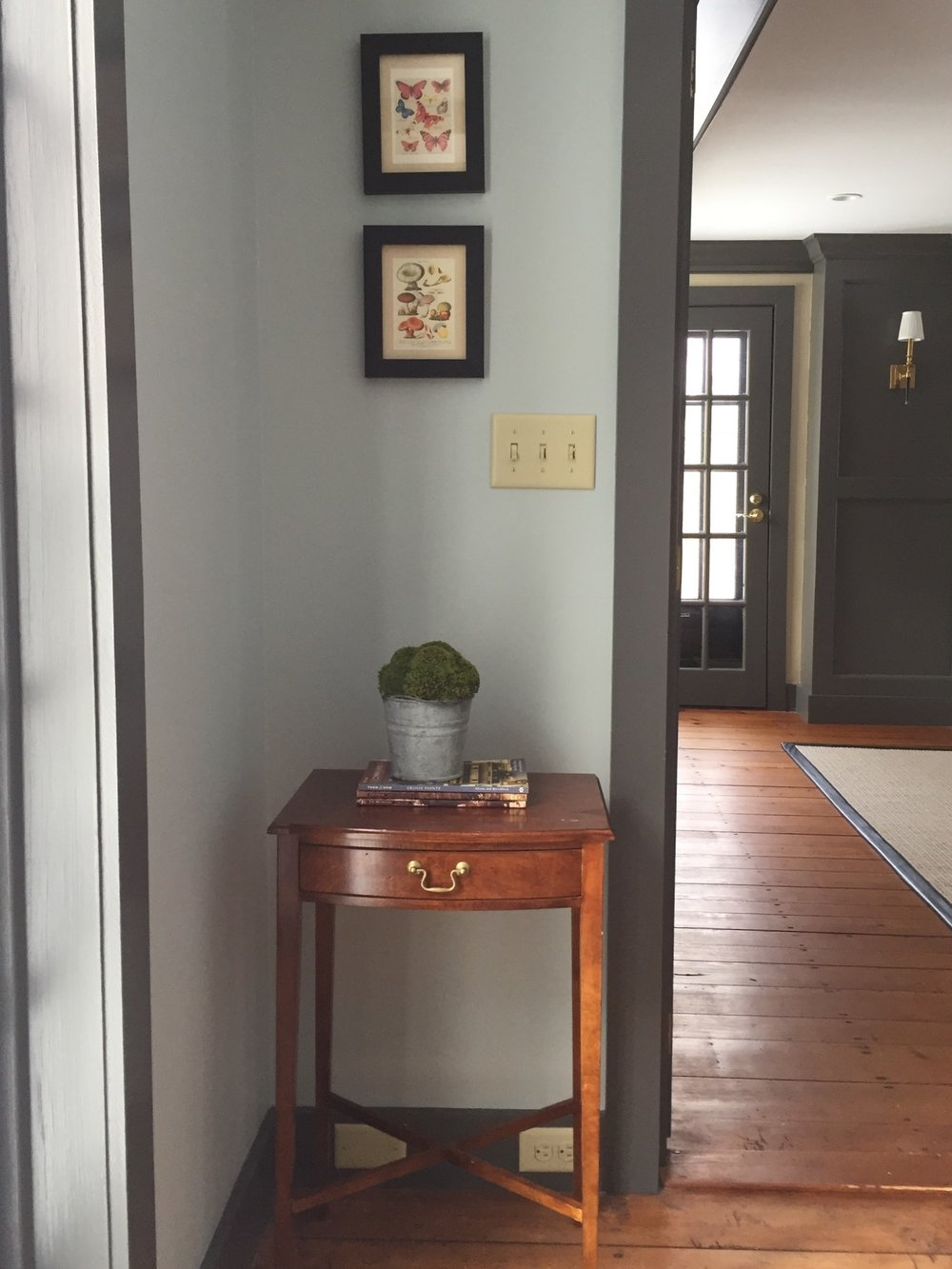 There wasn't much space here, but we could fit this antique side table next to the door. It's just enough space to drop the mail or your keys. The trim color (Benjamin Moore's Kendall Charcoal) is a nice contrast to the walls and helps to define this cozy space.