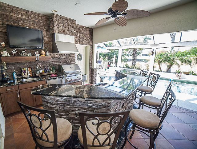These clients are ready for fall entertaining 🍂 🏈 🔥 -- football on tv, steaks on their (@twineaglesgrills ) grill, fully stocked (custom weatherproof resin kast) cabinets, with fresh cocktails sitting atop the granite bar and friends lined up on barstools brushing against (and admiring) the @eldoradostone stacked stone. .(see our FB page for more project photos). .  #readyforfall #outdoorentertaining #outdoordesign #outdoorliving #eldoradostone #twineaglesgrills #outdoorkitchen #outdoorcabinetry #summerkitchen #customcabinetry #buildingexcellence