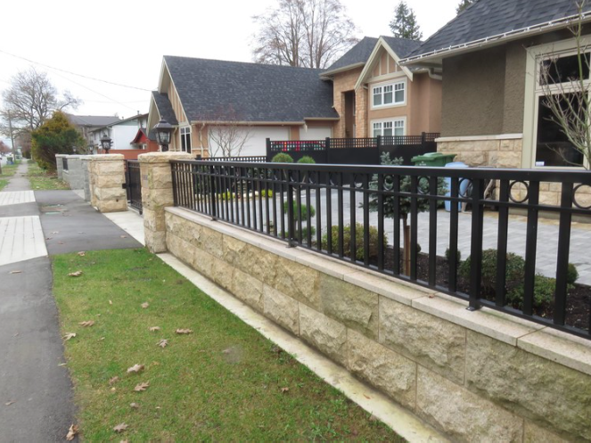 "Aluminum rail on top of retaining wall with 1.5""x5/8"" pickets and rings, Richmond, BC"