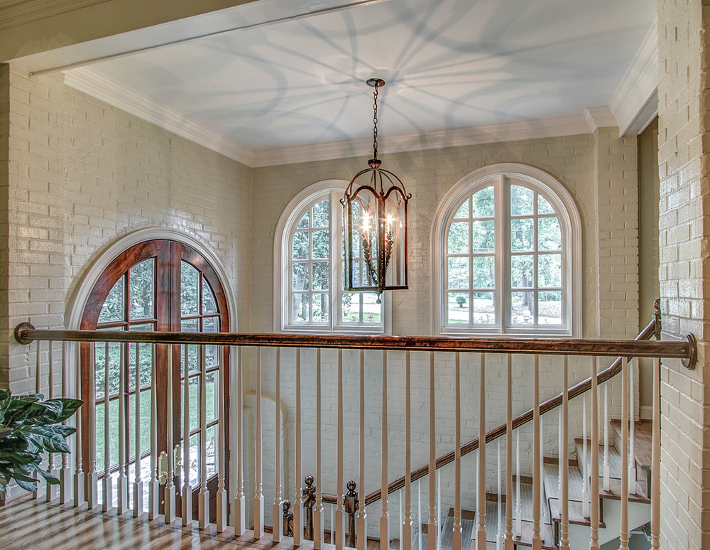 Brick Foyer with stairway and arched door