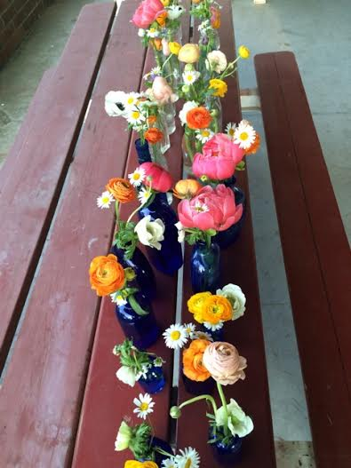 More flowers arranged in vintage bottles of all shapes and sizes.