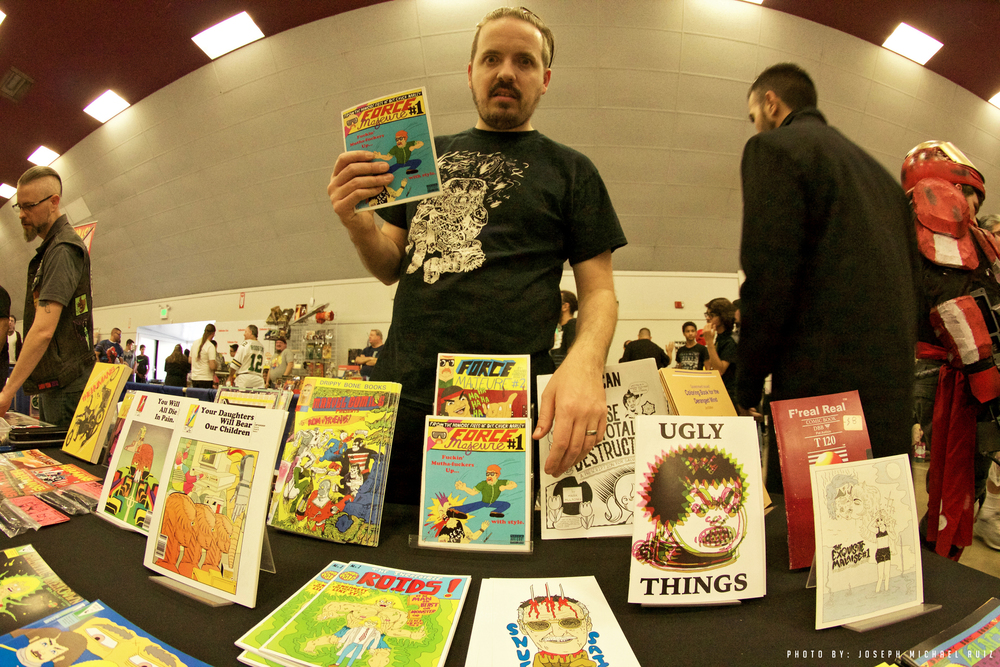 Keenan Marshall Keller with a bunch of comics from his micro publishing imprint, Drippy Bone Books and holding issue #1 of his series, Force Majeure.