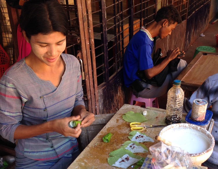 A Bamar woman wears Thanaka paste on her face at a jade market in Mandalay. She prepares traditional Betel nut packages while a jade worker on break peruses his cell phone.