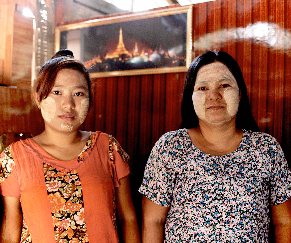 Ai Mon stands here with her mother, Aye Aye, in their living room. As devout Buddhists, they decorate their home with many holy images including the one behind them of Shwedagon Pagoda —the largest and holiest Buddhist monument in Myanmar.