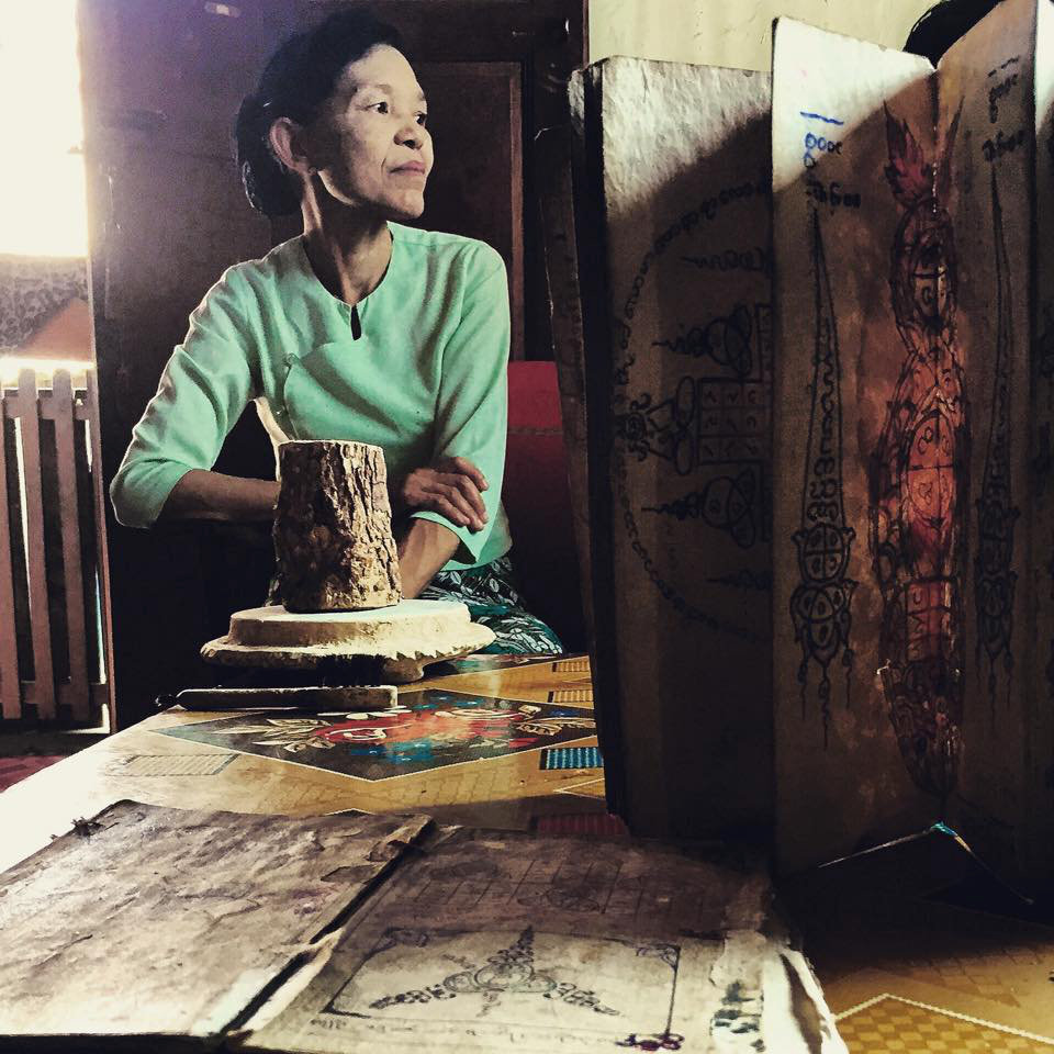 Daw Khin Aye sits in the company of her Thanaka log and grinder along with her husband's   century-old traditional tattooing books passed down from his grandfather  .