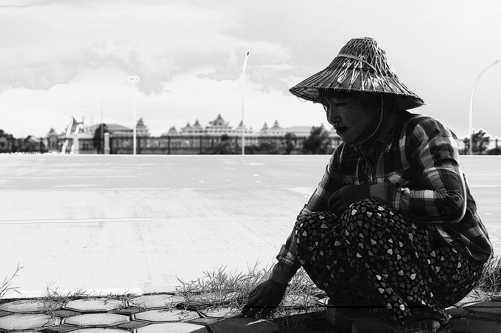 Ma Ni Myint works as a landscaper outside Myanmar's Parliament compound.She methodically pulls out weeds by hand to clean the cracks of the elaborate sidewalks that rim the dividing 16-lane highway.