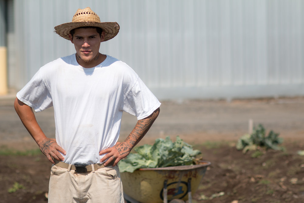 An incarcerated individual stops to pose to initiate a picture while working in the vegetable garden.