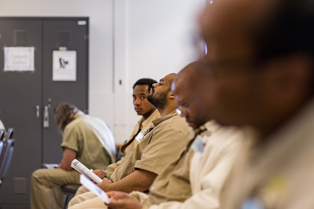 Rows of incarcerated individuals wait for a speech to begin by a formerly incarcerated individual-turned-college graduate and SPP intern.