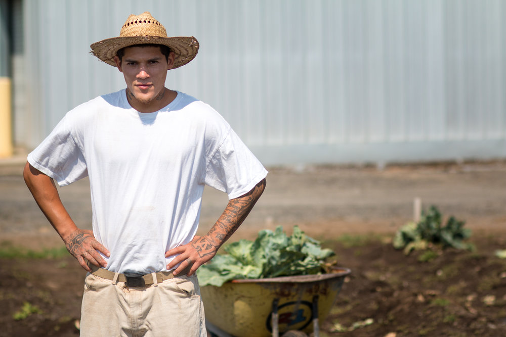 An incarcerated individual stops to pose, initiating a picture while working in the vegetable garden.