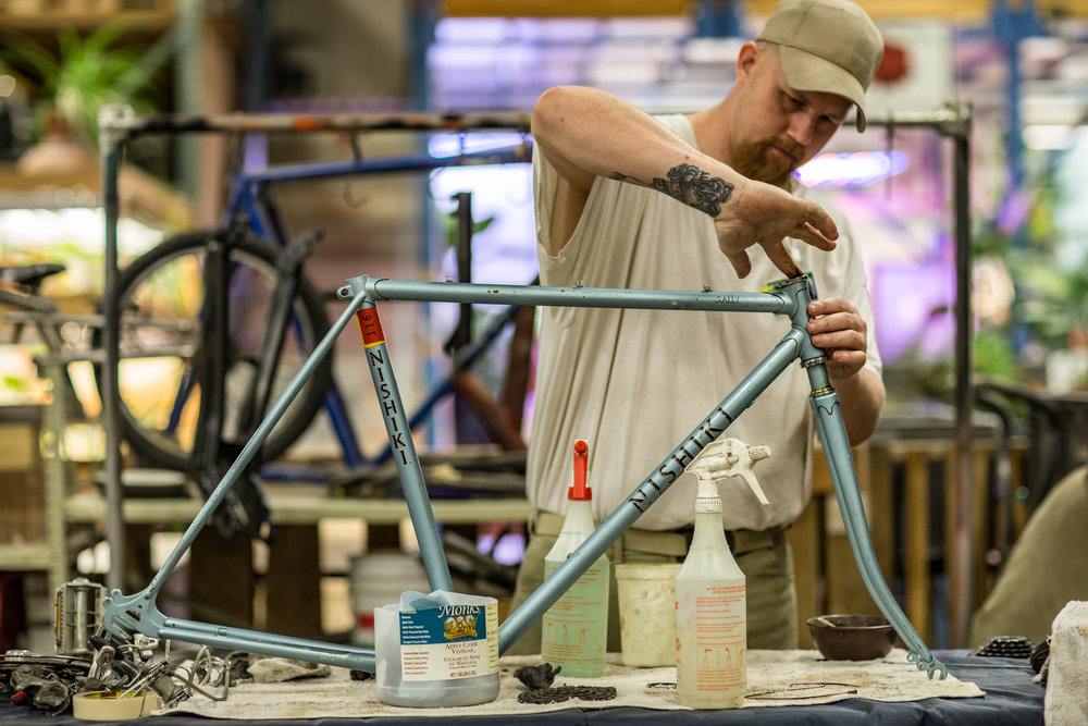 A bicycle repair technician at Washington State Penitentiary's Sustainable Practice Lab assembling a bike frame.