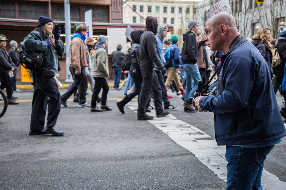 A photographer captures the protest with a medium format film camera.