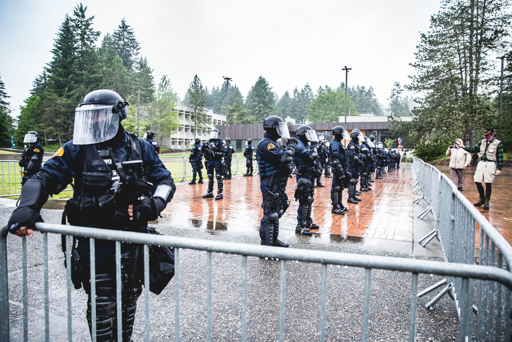 About 65 Washington State Patrol troopers in riot gear armed with rifles arrived on campus providing a divide between two opposing groups.