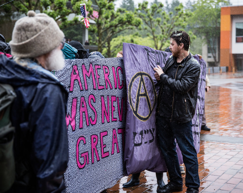 """Protesters used signs to plow """"free speech advocates"""" away, pushing them further and further away from the core of their group."""