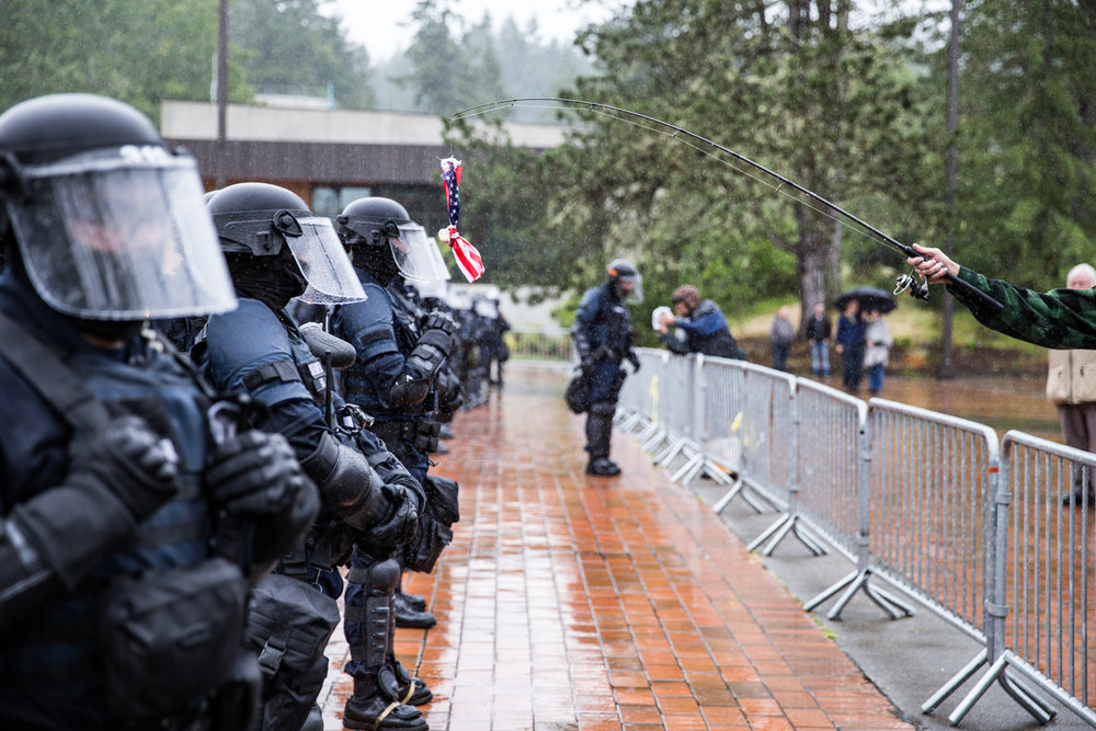 Police officers remain calm and motionless as a protester swings an American flag and a bagel in front of their face shields.