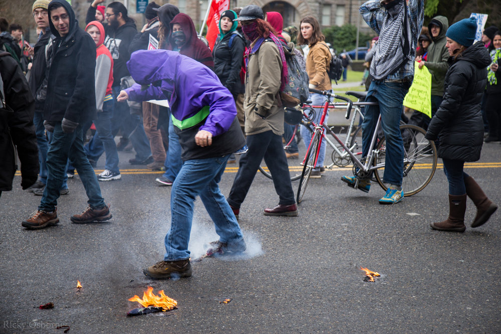 An individual tries to extinguish a burning flag.