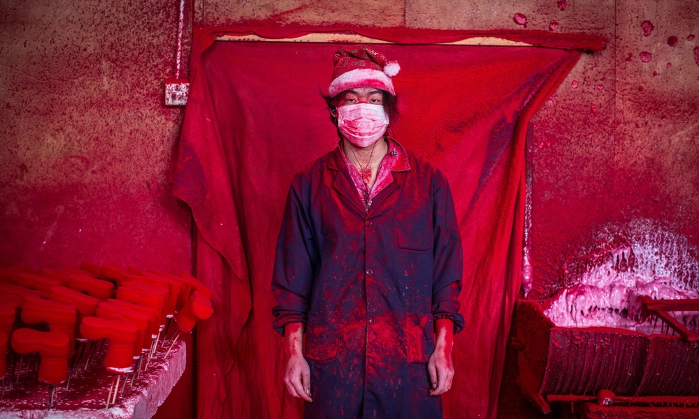 Worker producing Christmas decorations in Yi Wu, China. Photo by Toby Smith.