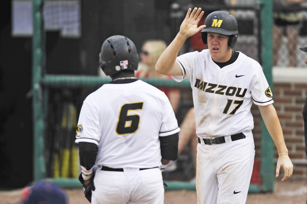 Missouri's Josh Lester reaches for a high five with Missouri's Trey Harris after they both cross home plate at Taylor Stadium in Columbia, Mo. on May 3, 2015. The Tigers lost 4-3.