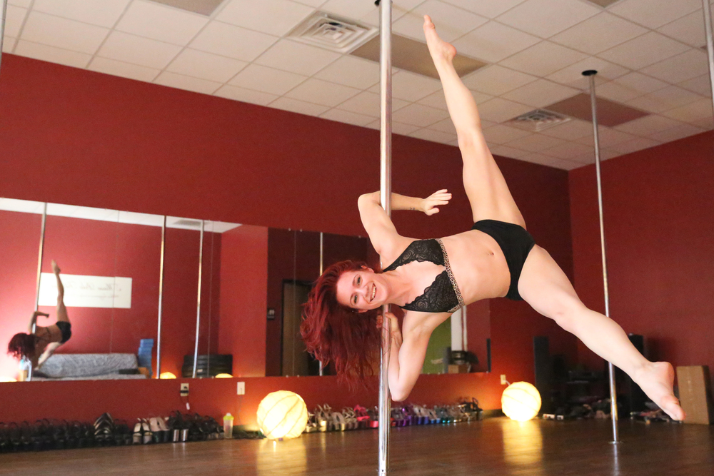 Jordan Mazur demonstrates a pole move at her studio, Muse Pole Fitness, on Wednesday, January 27, 2016.
