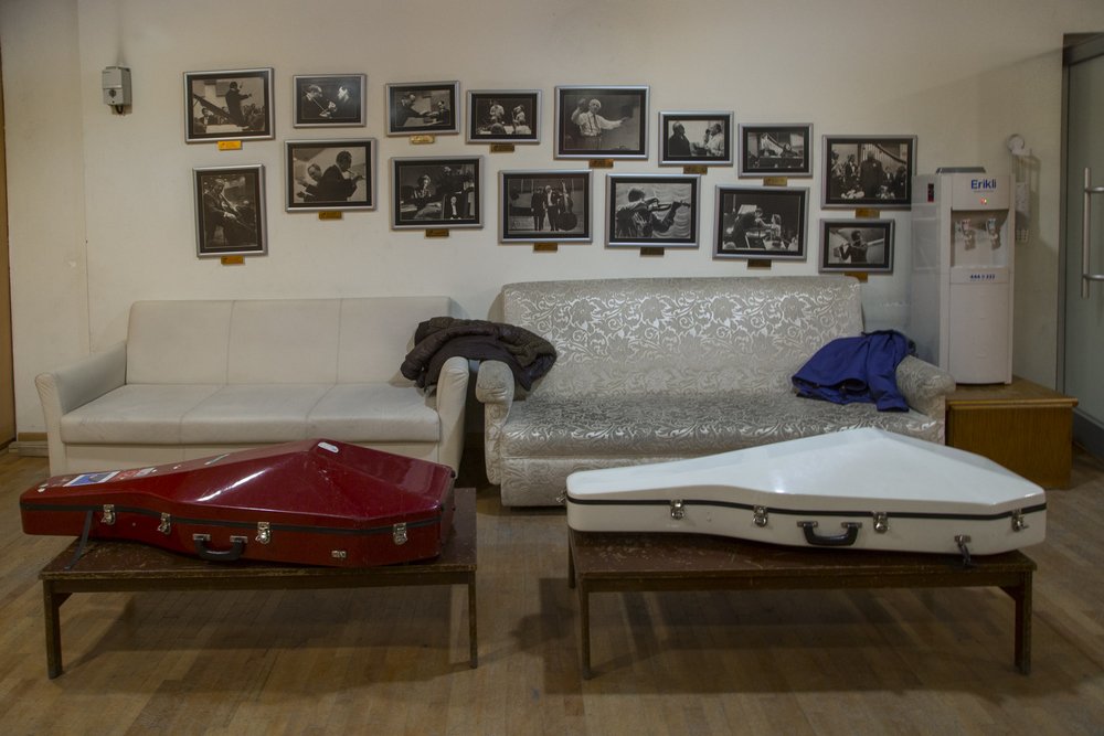 The CSO's backstage. Cases of cellos lie on coffee tables. Photos on the wall above them are that of previous performances with renowned musicians such as Yehudi Menuhin. Today, less well-known musicians collaborate with the orchestra. Ankara, 15th of December 2014.