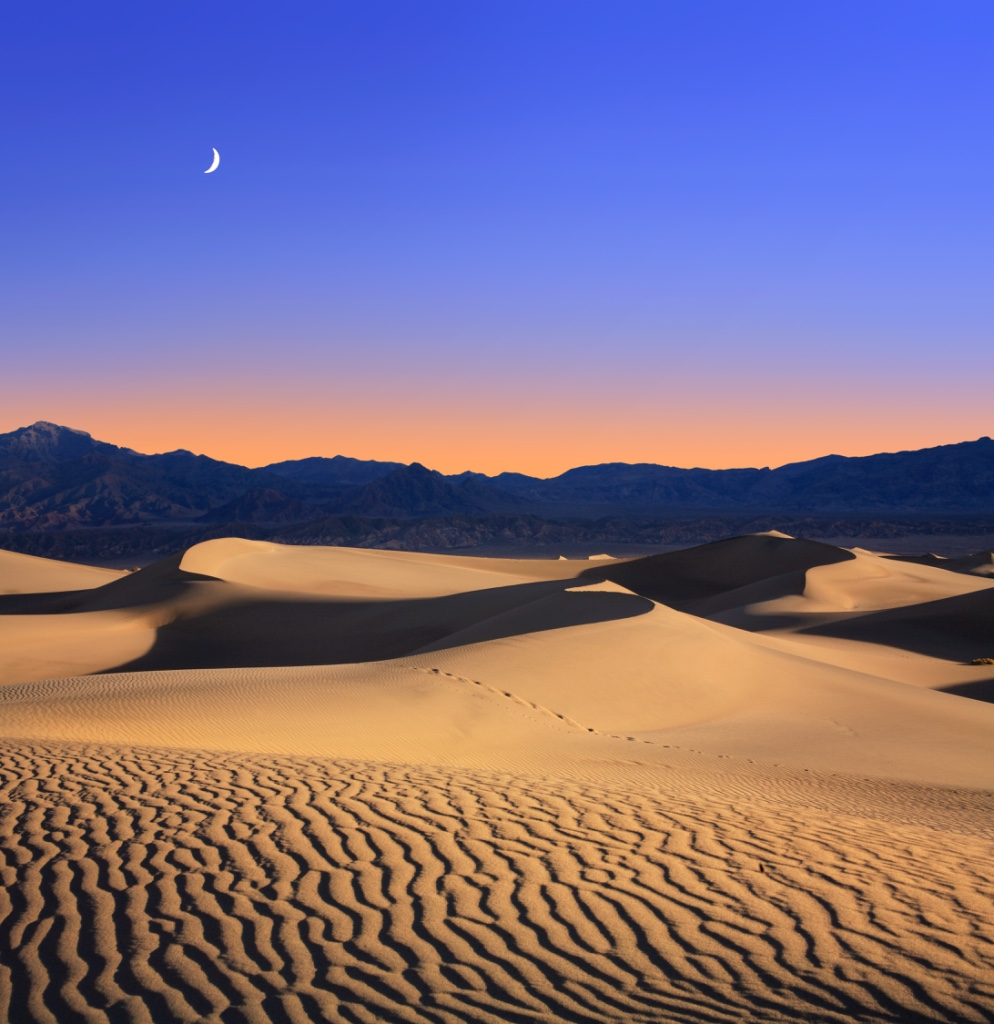 Early Morning Sunlight Merges With A Twilight Moon Over Sand Dunes And Mountains At Death Valley National Park - (PHOTO: DOUG LEMKE/SHUTTERSTOCK)