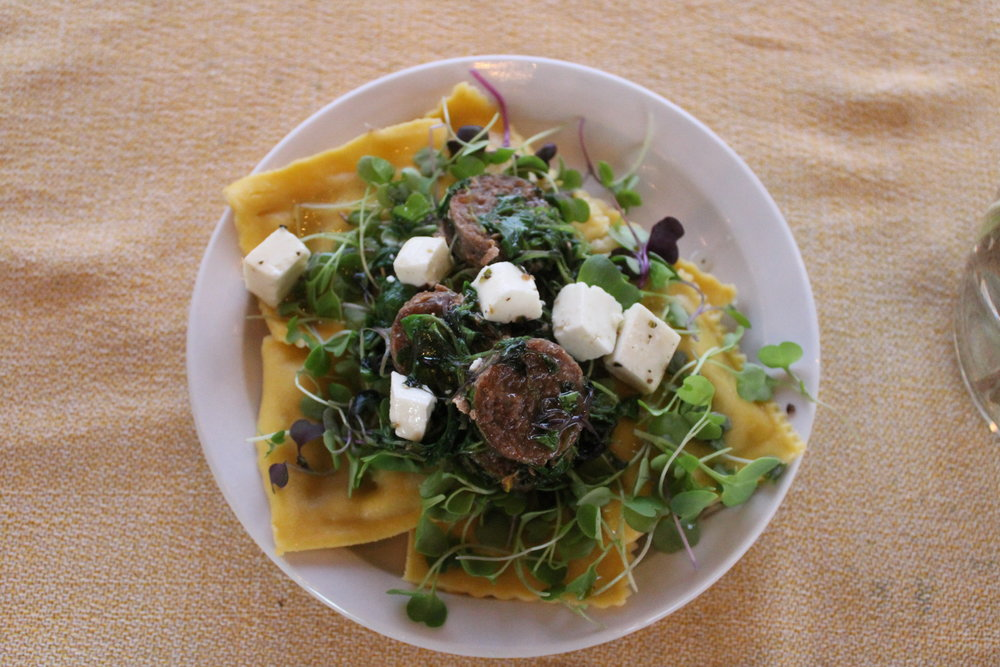 This is a City Roots Farmers Market meal, created off-the-cuff by farmer Keith Willoughby of Wil-Moore farms, using one pan, a hot plate, and ingredients from the market! You're looking at fresh butternut squash ravioli topped with garlic pork sausage (sautéed in a healthy pat of Happy Creamery butter), Trail Ridge marinated goat feta, and City Roots microgreens. Voila!